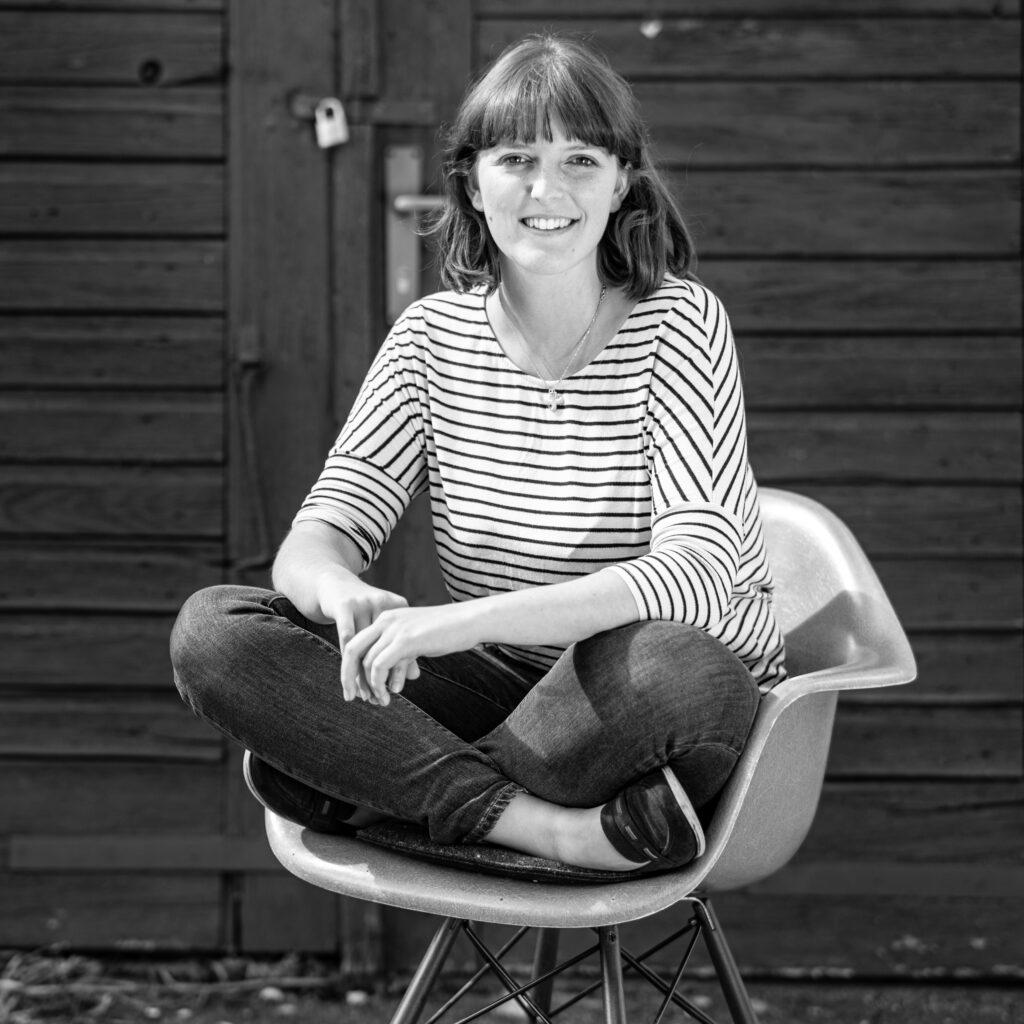 Katharina Gebauer mit gestreiftem oberteil im Schneidersitz auf einem Stuhl