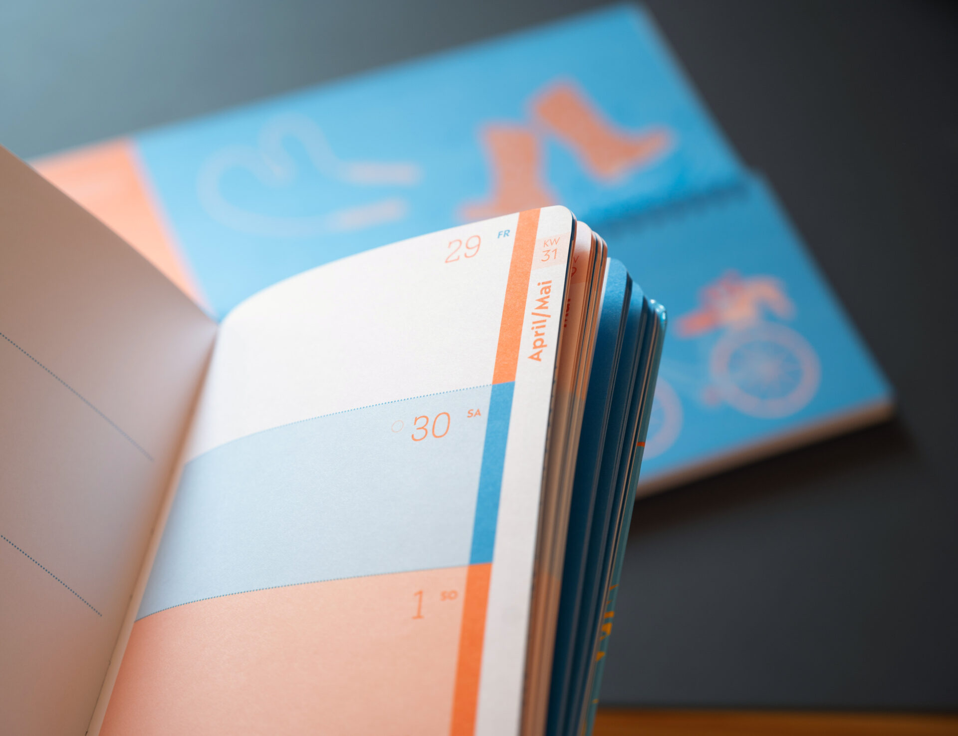 Produktfoto Kindergarten heute Tischkalender und Taschenkalender in Blau mit orangenen Figuren auf dem Cover