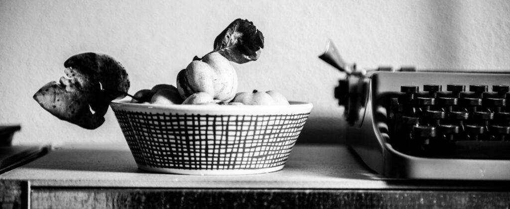 schwarz-weiß Bild mit Obstschale, in der Quitten liegen mit Schreibmaschine rechts daneben