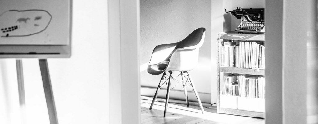 Schwarz-weiß Bild des lichtdurchfluteten Büros mit moderner Flipchart im Vordergrund und einem Designerstuhl im Hintergrund
