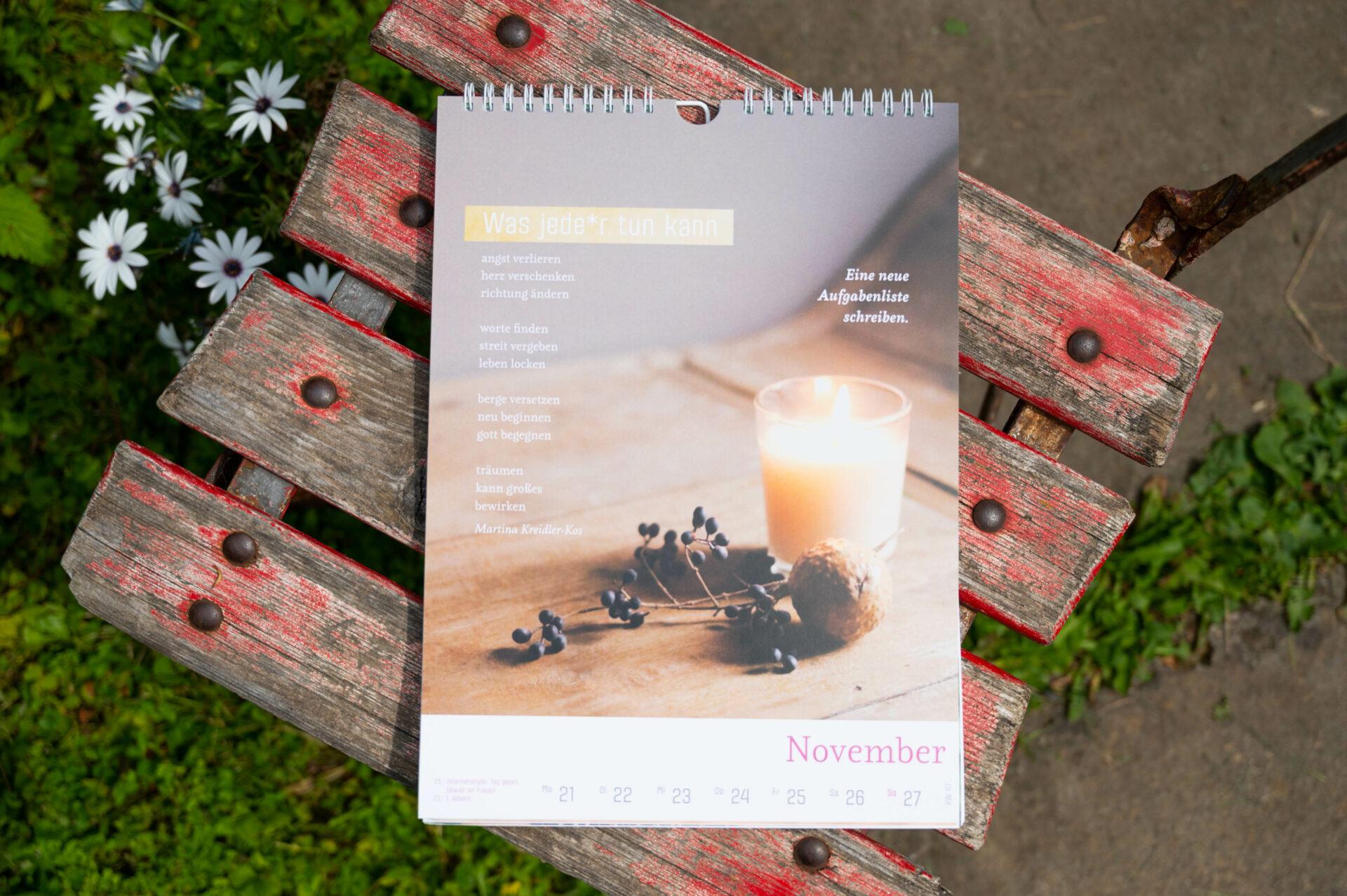 Kalenderblatt November auf altem Holzstuhl mit abgewetzter roter Farbe.