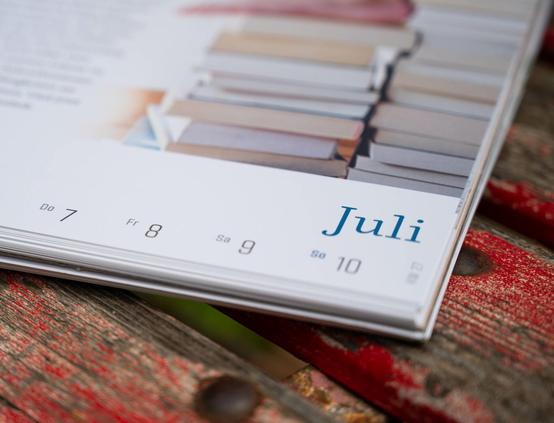 Detailaufnahme Kalenderblatt Juli auf einem alten Holzstuhl.
