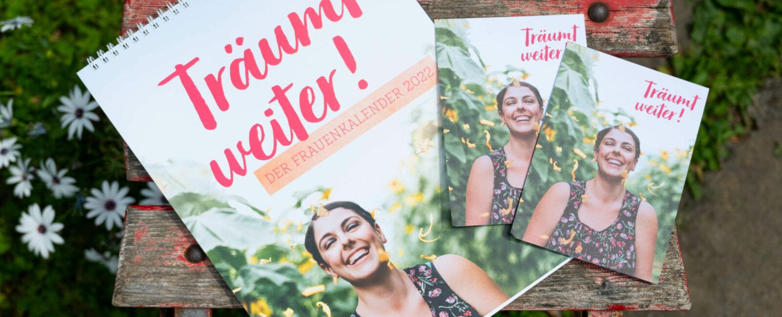 """Titelbild des Frauenkalender mit dem Titel """"Träum weiter"""" in rosa Schreibschrift und einer lachenden Frau im Sonnenblumenfeld."""